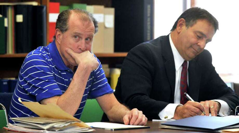 Dr. Robert Wollkind, left, sits with D. Randall DiBella, his attorney, during his termination hearing at Brookfield Town Hall in this file photo taken in February. Photo: Michael Duffy