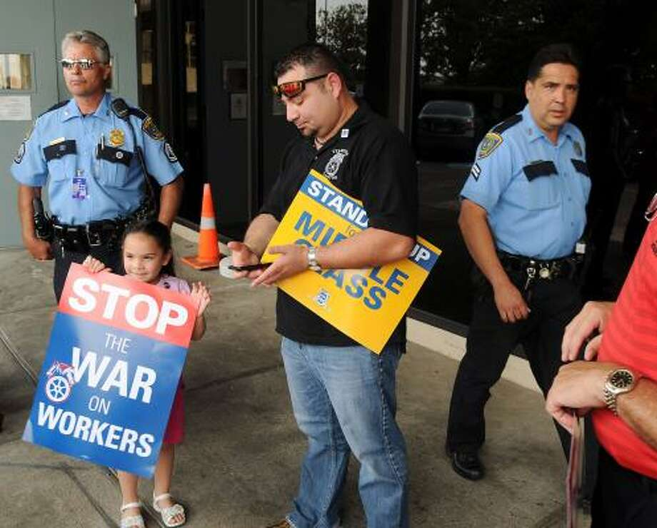 Local Teamster member Jorge Lizama and his daughter Hailey are asked to leave the property of the Marriott at Bush Intercontinental Airport after protesting the visit of U.S. Rep. John Mica, R-Fla., while he was attending an I-69 meeting. Photo: Dave Rossman:, For The Chronicle