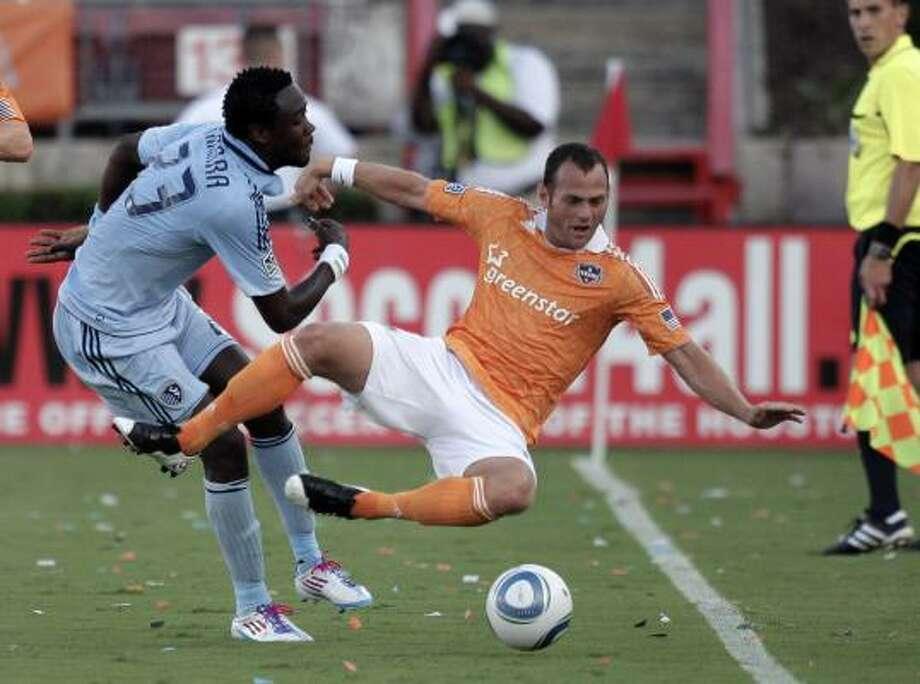 Former Dynamo forward Kei Kamara knocks Dynamo midfielder Brad Davis off the ball. Photo: Bob Levey, Getty