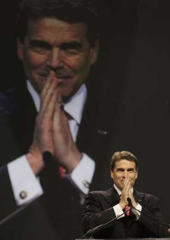 Texas Gov. Rick Perry took the stage Saturday to read Scripture and lead a prayer. The seven-hour program of faith and fasting was funded by the American Family Association. Photo: Melissa Phillip, Chronicle