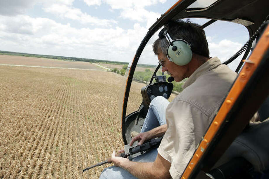 Jimmy Meyer flies with his brother, Joseph Meyer, of Flying J Services, over a cultivated field in search of feral hogs. They are hired to eliminate wild hog populations. Photo: Jerry Lara, San Antonio Express-News