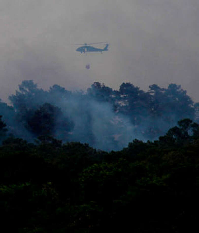 "Crews on the ground this week got help from above in fighting the fast-moving Dyer Mills wildfire in Grimes County, including this helicopter that flew in to target a hot spot on Monday about three miles east of Whitehall. Grimes was not among the 45 counties that FEMA granted ""major disaster"" status on Friday. Photo: Mayra Beltran, Chronicle"