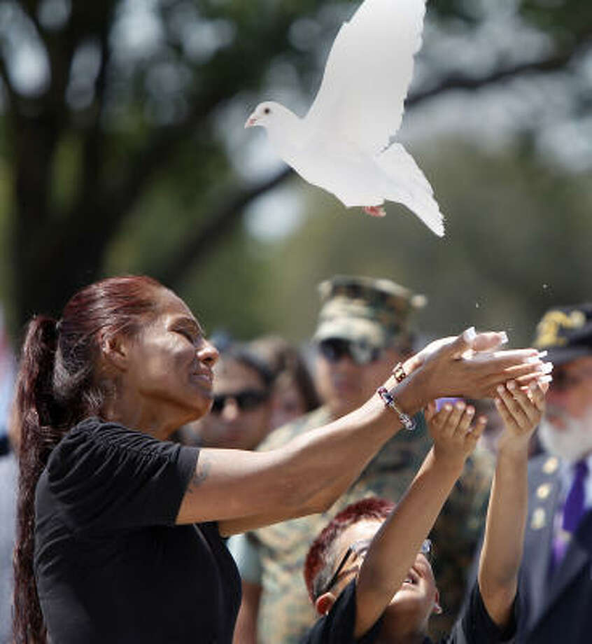 Janie Torres, mother of Army Sgt. Jacob Molina, releases a dove with her youngest son, Shawn Carreon, during burial services Monday at the Veterans Memorial Cemetery. Photo: Karen Warren, Houston Chronicle