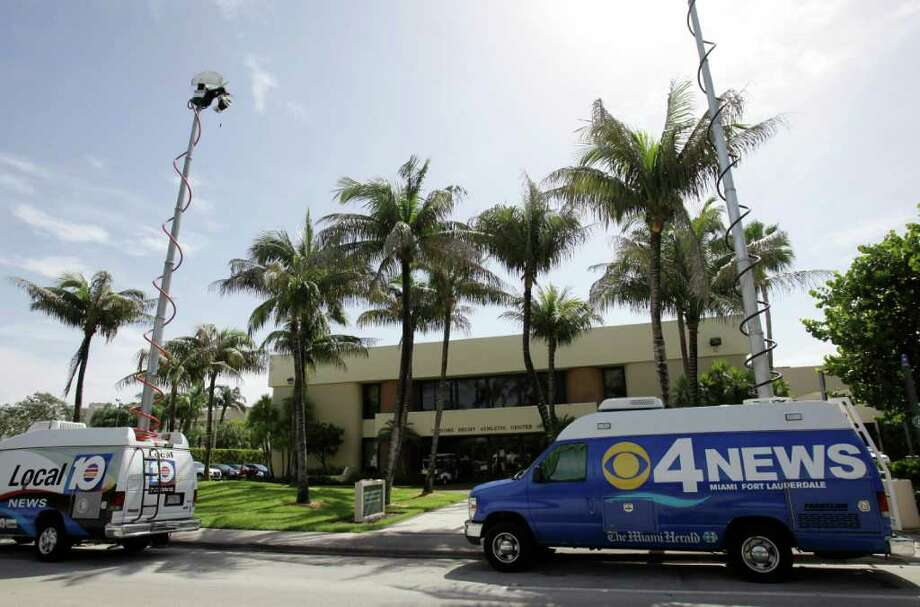 Television trucks are parked outside of the University of Miami Isadore Hecht Athletic Center in Coral Gables., Fla., Wednesday, Aug. 17, 2011. NCAA investigators were on campus this week to investigate an account by former booster Nevin Shapiro, who claims he treated football players with sex parties, nightclub outings, cars and other gifts. (AP Photo/Lynne Sladky) Photo: Lynne Sladky, STF / AP