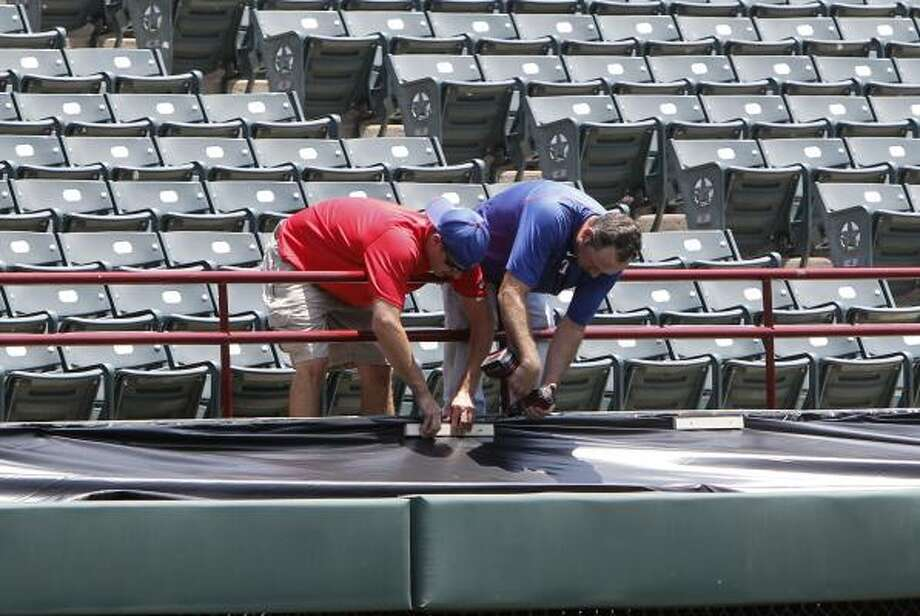 On Friday, workers fasten a tarp on the area where firefighter Shannon Stone fell at Rangers Ballpark in Arlington on Thursday night. Stone tumbled over a railing and plunged 20 feet onto concrete below and died at a hospital a short time later. Photo: LM Otero, Associated Press