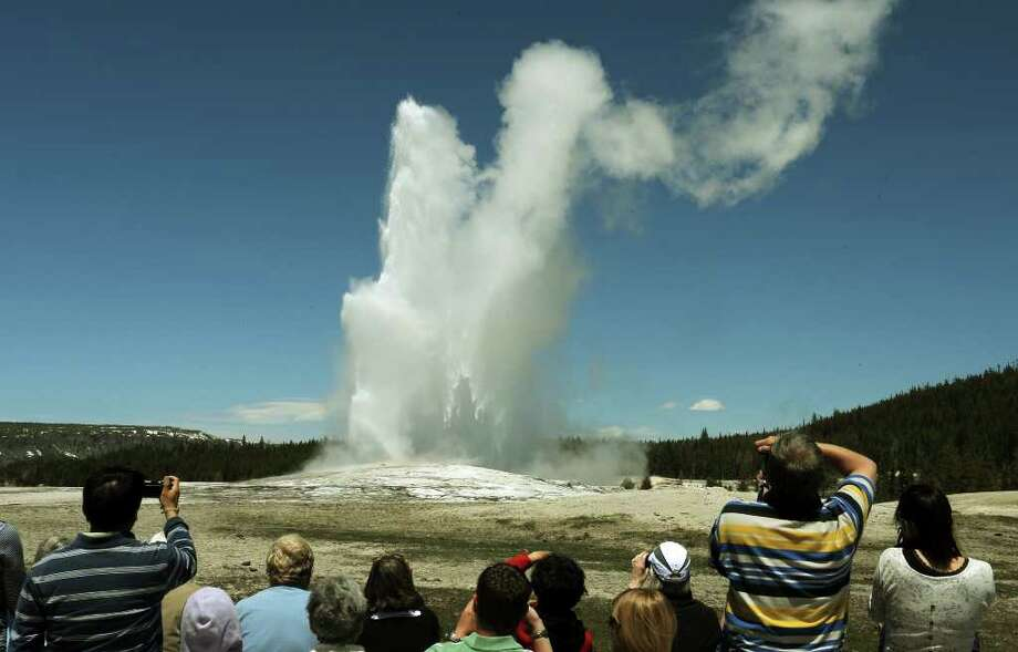 Tourists watch the 'Old Faithful' geyser which erupts on average every 90 minutes in the Yellowstone National Park, Wyoming on June 1, 2011. AFP PHOTO/Mark RALSTON  Photo: MARK RALSTON, Staff / AFP
