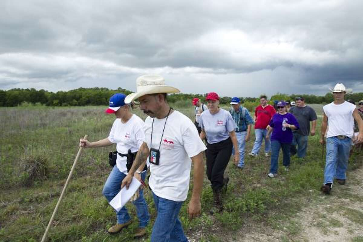 Eddie Arguijo, front, a field coordinator with Texas Equusearch, leads a group back to their vehicles after combing a field Friday.