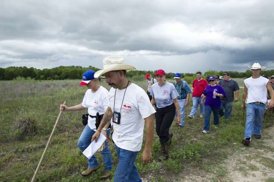 Eddie Arguijo, front, a field coordinator with Texas Equusearch, leads a group back to their vehicles after combing a field Friday. Photo: Nick De La Torre, Chronicle