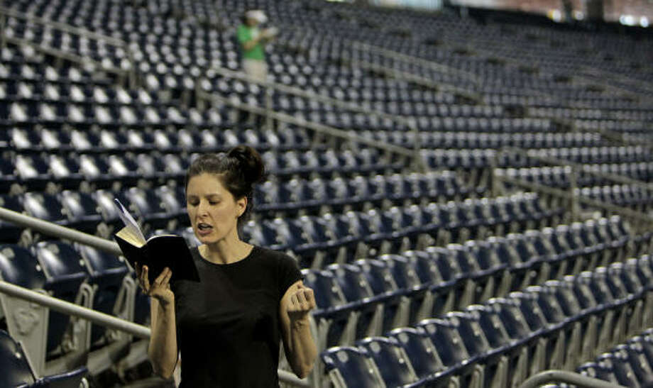 Natasha Solce, of Houston, reads from the Bible as she and other volunteers blessed and read Scripture over chairs at Reliant Stadium Friday in preparation for The Response. Photo: Melissa Phillip, Houston Chronicle