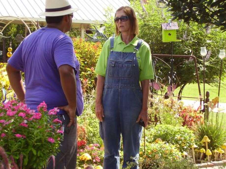 Beverly Welch talks with Oswald Diaz during a break from customers. Welch said her employees all share a love of plants and gardening. Photo: Bryan Kirk