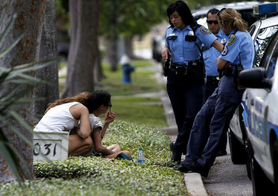 Houston Police officers interview two women in the 2000 block of Banks Street, where a 24-year-old woman was found dead in a pool on Sunday. Photo: Karen Warren, Chronicle