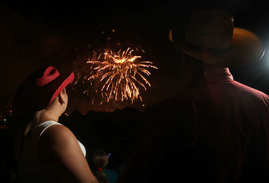 it's a hot holiday Irma Garcia, left, watches last year's Freedom Over Texas fireworks show. Because of extreme drought conditions, some surrounding communities have canceled their fireworks display to avoid any fire hazards. Photo: Mayra Beltran, Houston Chronicle