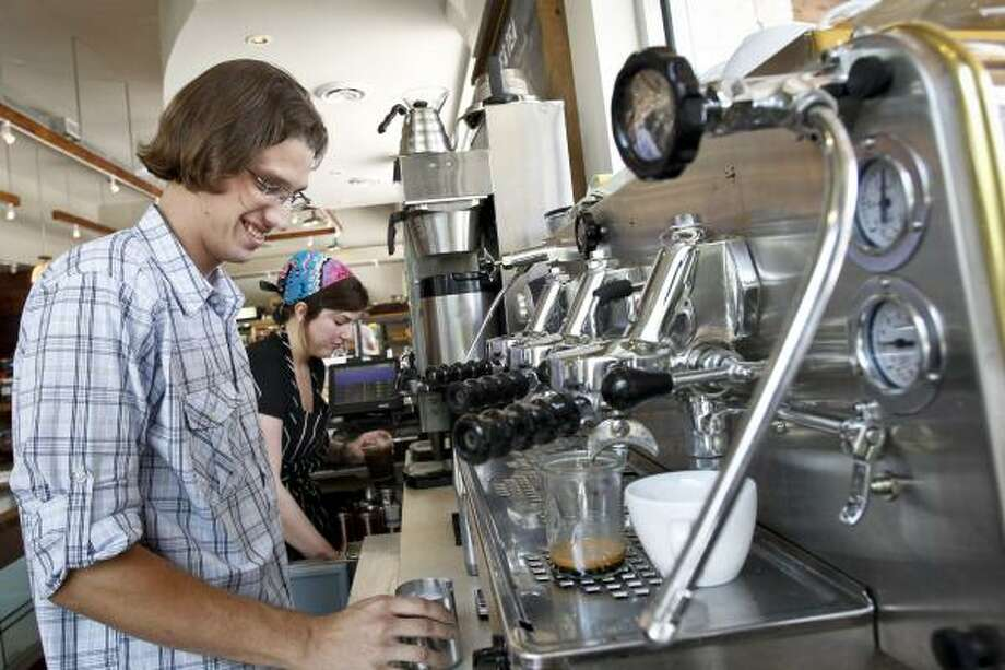 Barista, Fabio Pontes, makes an espresso behind the coffee bar at Revival Market in the Heights. The grocery is one of the few places in town where you can get locally roasted coffee from a handful of the city's top roasters. Photo: Michael Paulsen, Houston Chronicle