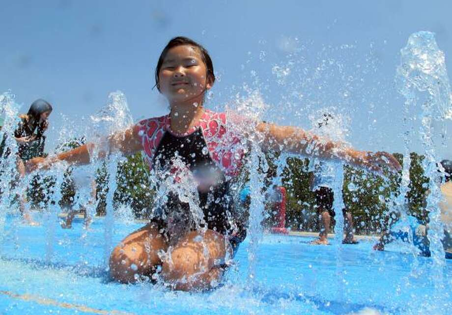 Yue Lu, 6, enjoys splashing in Nottingham Park. Temperatures hovering at triple digits are keeping splash parks popular. Photo: Melissa Phillip, Houston Chronicle