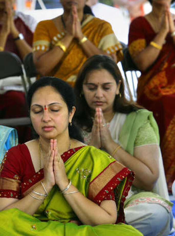 asundhara Vedala, foreground, and Hema Chudasama pray at the new Hindu Temple of The Woodlands. Photo: Cody Duty, Chronicle