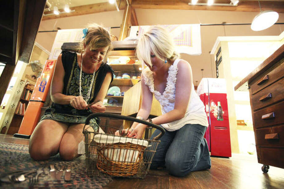 Brandi Dunagan, left, and Maggie Clifton of Country Sugar Events in San Antonio look through a basket of vintage silverware. Dunagan said she was inspired to start planning sustainable weddings after seeing how much was spent and wasted in high-priced events. Photo: Andrew Buckley, San Antonio Express-News