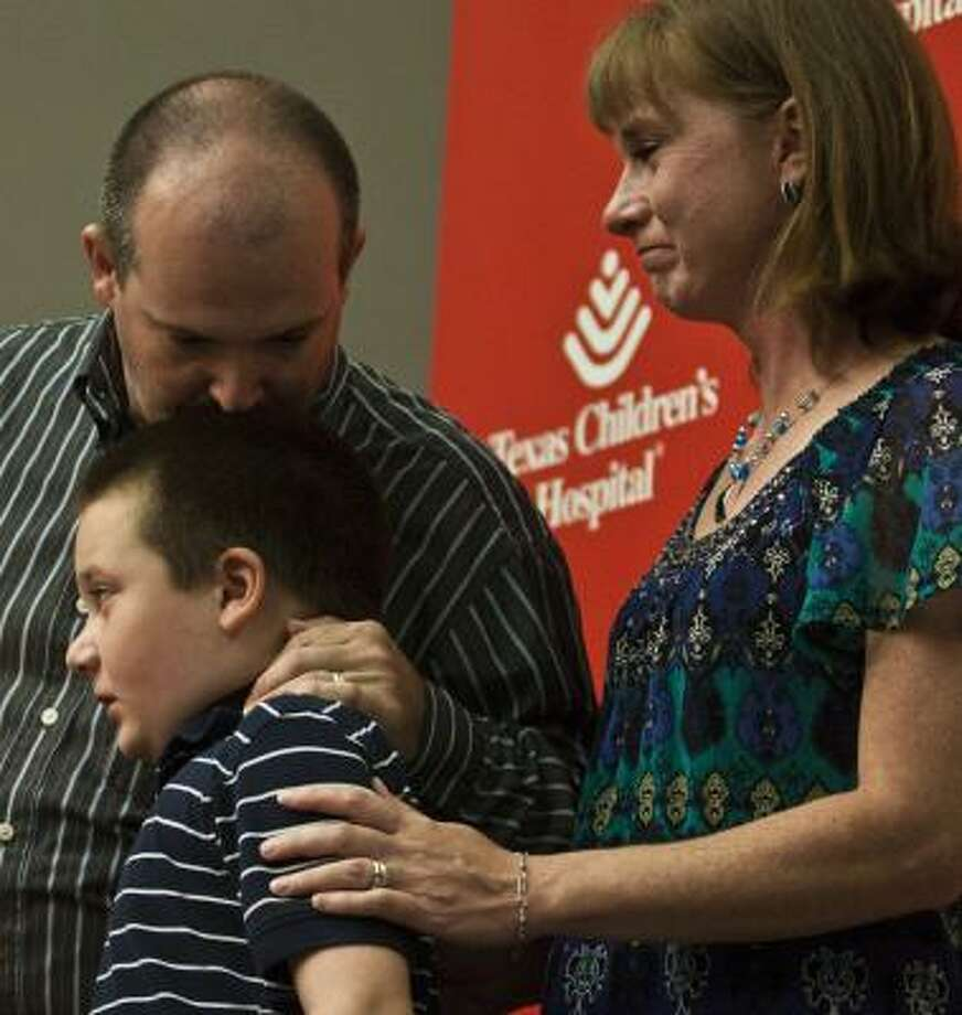 Keagan Dysart, 9, and his parents, Khris and Robin Dysart, speak during a Monday presentation on the surgery used to help cure Keagan of his epileptic seizures. Photo: Eric Kayne, For The Chronicle