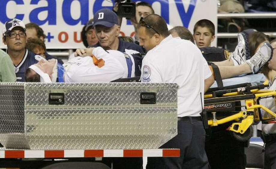 Dallas Cowboys wide receivers coach Jimmy Robinson is taken off the field as team owner Jerry Jones, center,  looks on after Robinson was injured after being run into by a player during training camp on Saturday in San Antonio. Photo: DARREN ABATE, Associated Press