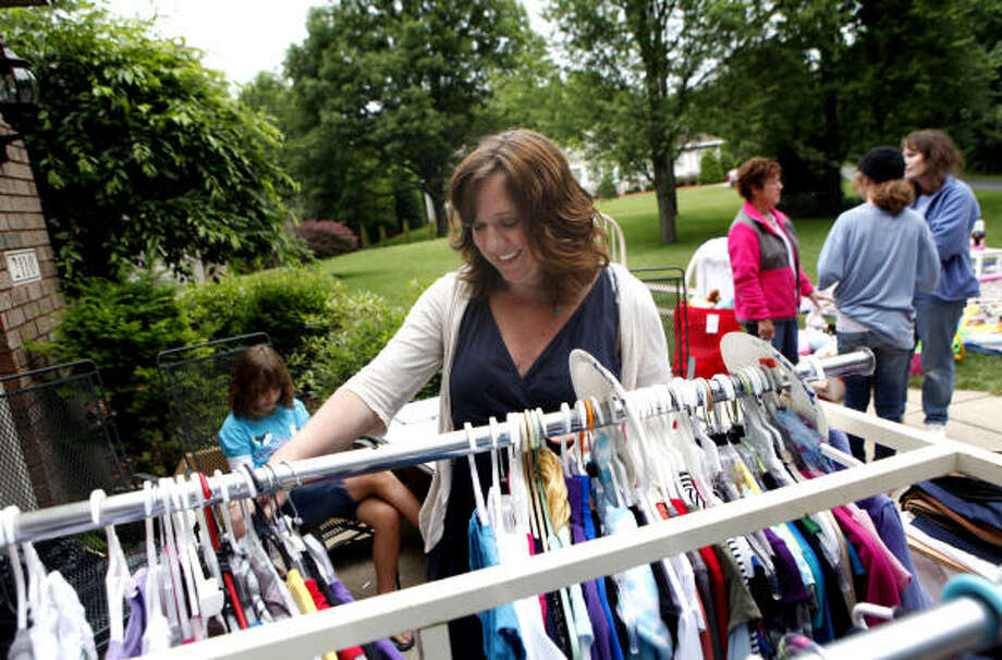 Author Lorilee Craker looks through shirts at a yard sale in Grand Rapids, Mich., as part of her attempt to live out her new book, Money Secrets of the Amish. Photo: EMILY ZOLADZ, THE GRAND RAPIDS (MICH.) PRESS