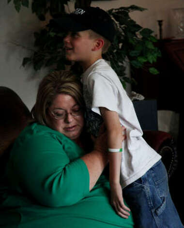 Dana Janczak listens to her 10-year-old son Nathanael's chest after his pulmicort treatment in their rural Cleveland home. Janczak said she and her children suffer from asthma and find access to a doctor difficult. Photo: Mayra Beltran, Chronicle / HC