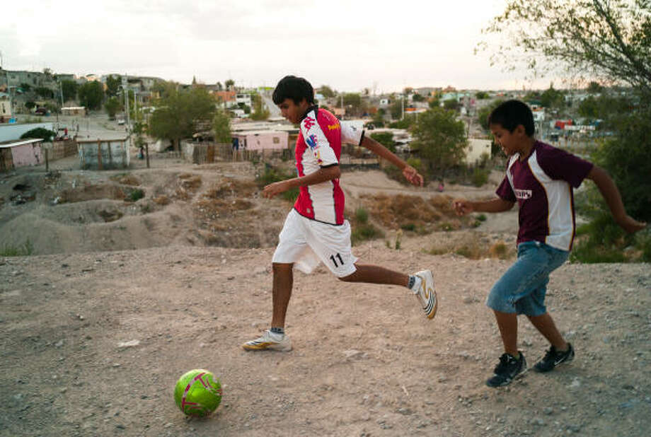 Cousins of young slaying victim Ernesto Acosta play soccer in the dirt yard in front of their home on Juarez's west side rather than risk playing in the new field nearby that is on another gang's turf. Photo: Julian Cardona, Chronicle