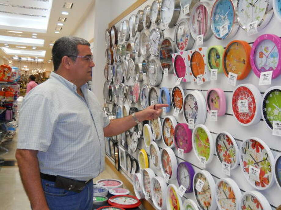 Venezuelan shopper Fernando Castro checks out a wall of clocks at the May's depart-ment store. He was buying for a store his mother runs. Photo: Jenalia Moreno:, Chronicle