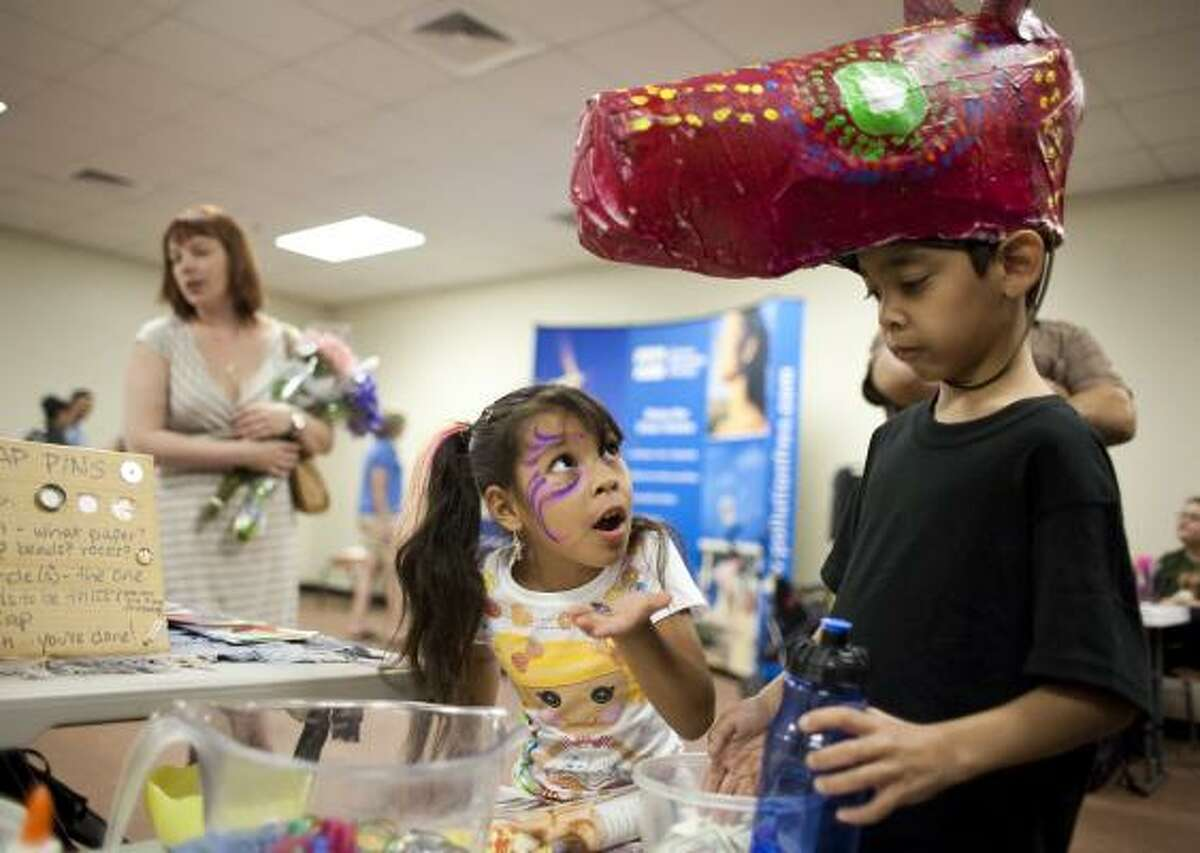 Gya Llanas, 5, left, of Houston, asks for another bottle cap as she and Constantino Martinez, 8, of Houston, make bottle cap pins during the Green Arts Festival Saturday in the East End.
