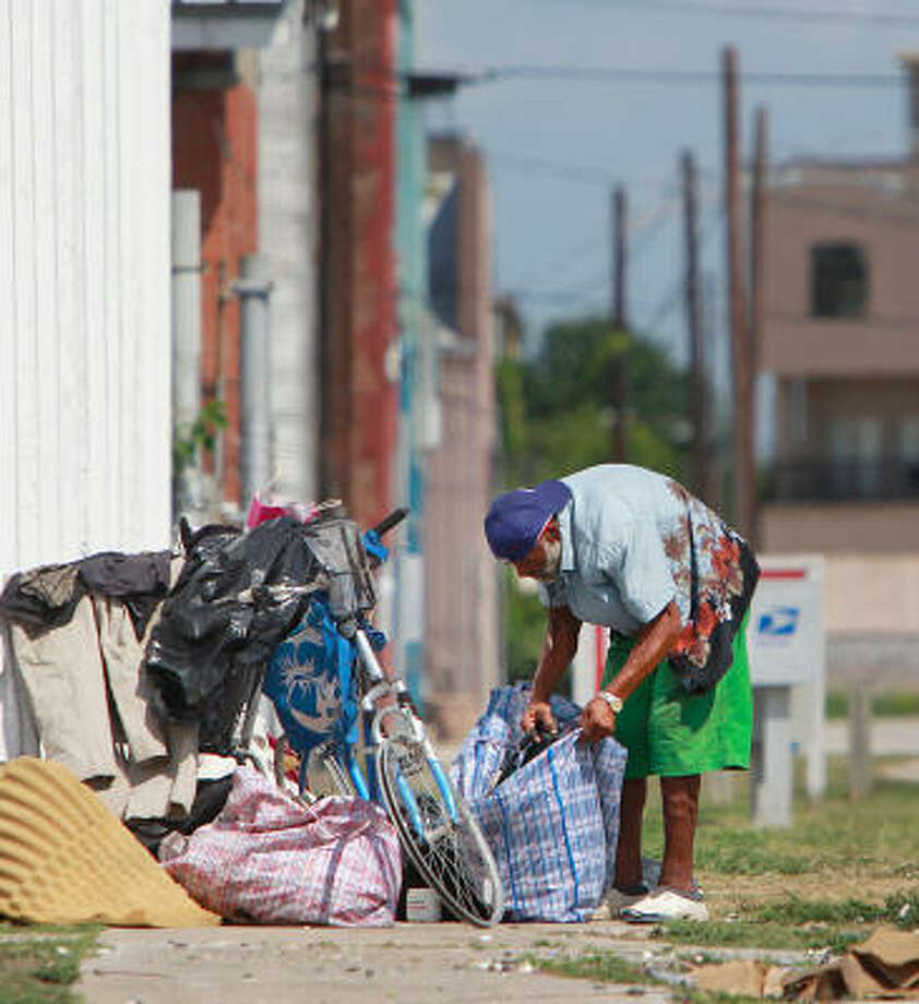 C.J. stows his belongings at a corner along St. Emmanuel and Congress on Wednesday. East Downtown residents have petitioned to have their neighborhood added to the city's anti-loitering ordinance, which prohibits sleeping on sidewalks. Photo: Mayra Beltran, Chronicle