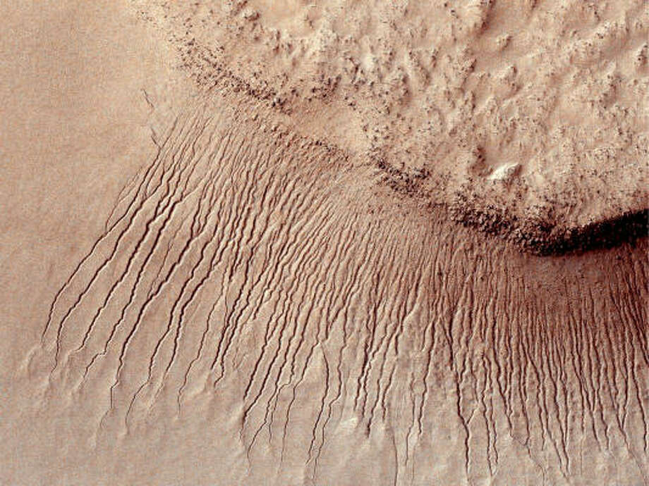 Scientists believe these lines seen on some slopes on Mars may be evidence of flowing salt water. Photo: Getty