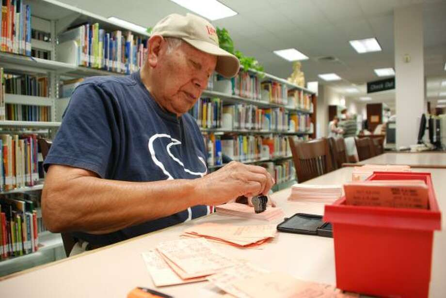 LINDSAY PEYTON: FOR THE CHRONICLE PLENTY TO PROCESS: John Brown updates a batch of library due date cards at the South Branch Library in The Woodlands. Library use in the county has increased, with 43 percent of the population registered in the library's system.  LINDSAY PEYTON: FOR THE CHRONICLE PLENTY TO PROCESS: John Brown updates a batch of library due date cards at the South Branch Library in The Woodlands. Library use in the county has increased, with 43 percent of the population registered in the library's system. Photo: Lindsay  Peyton, For The Chronicle