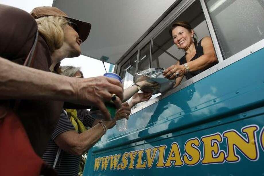 Sylvia Casares, dueña de dos restaurantes mexicanos en Houston, atiende a sus clientes desde la evntanilla de su camión de comidas, No Borders, localizado en un estacionamiento justo al lado del Museo Menil, donde la taquería ambulante está jueves y viernes. Su camión es uno de los nuevos negocios de comida ambulante que ofrece diversidad en el menú, mejor presentación y sirve en fiestas privadas y eventos. Photo: Johnny Hanson, La Voz