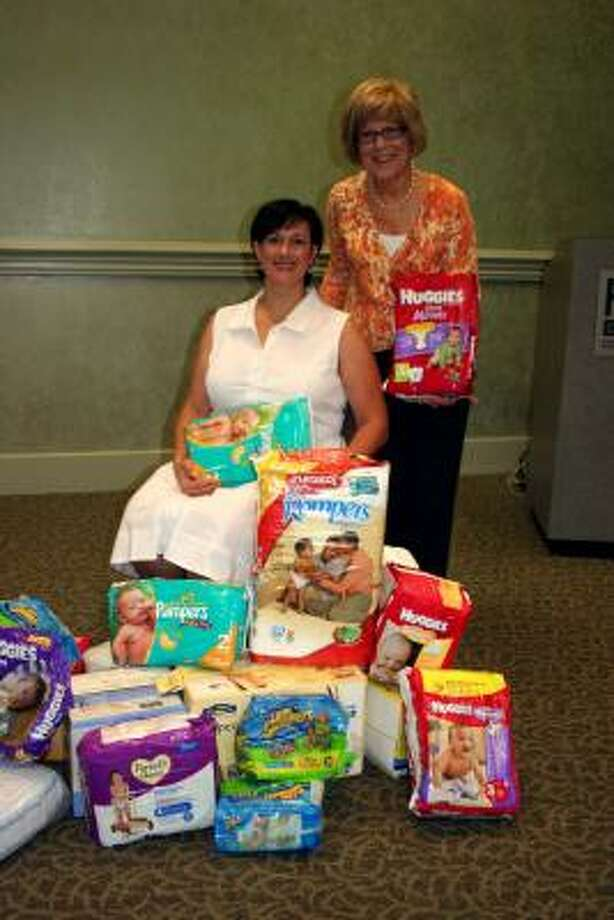 LEADING THE EFFORT: Melissa Cola, seated, is surrounded by some of the diapers she collected in a drive last spring. With her is Dee Koch, who hosted the thank you-luncheon on July 22. Photo: Joan Vogan, For The Chronicle