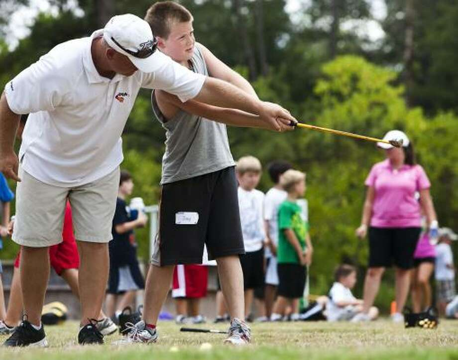 David Bergeron, left, is happy to offer help to Joey Dunlap at a camp in The Woodlands. Photo: Patrick T Fallon, Chronicle