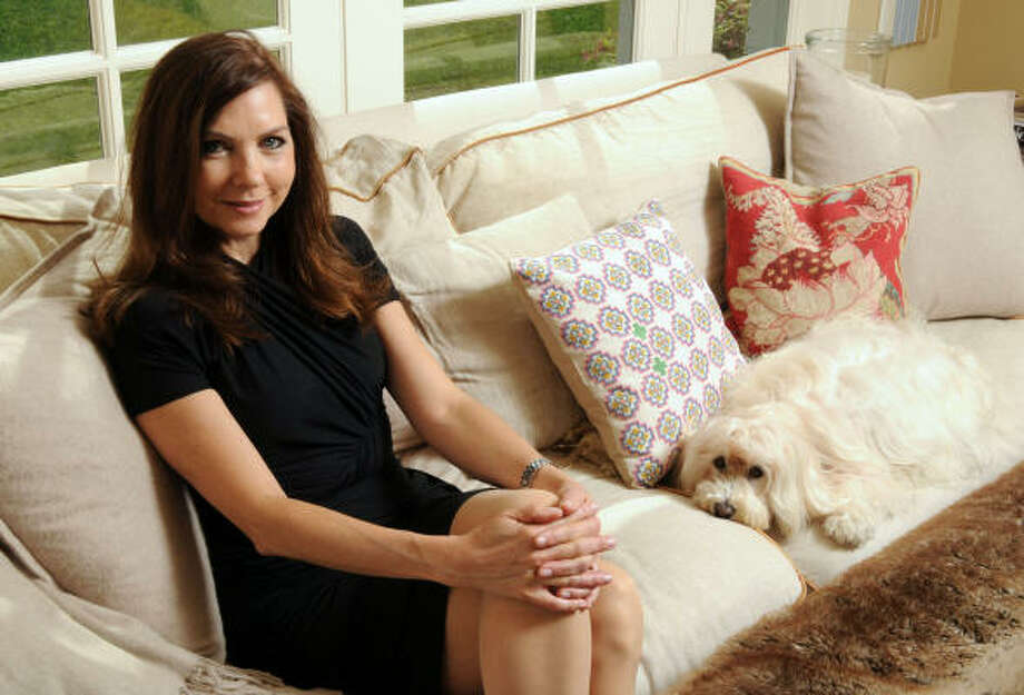 Although she's a contemporary gal at heart, Rottet (with Havanese pooch Sammy) loves the relaxed comfort of her home's traditional sunroom, which overlooks the pool. Photo: Dave Rossman, For The Chronicle