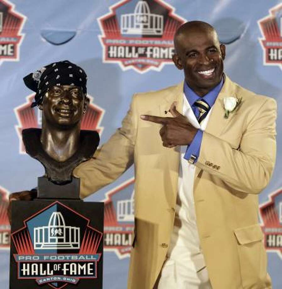 Deion Sanders poses with his Pro Football Hall of Fame bust after the legendary corner added his trademark bandana to it. Photo: Tony Dejak, Associated Press