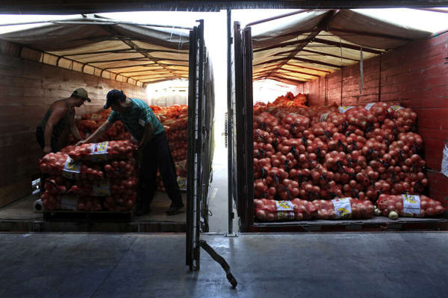 Jesus Valenzuela and Gregorio Avila move bags onto a truck at Progreso Produce in Pharr. Mexico sends more produce to the U.S. than any other country. Photo: Lisa Krantz :, San Antonio Express-News