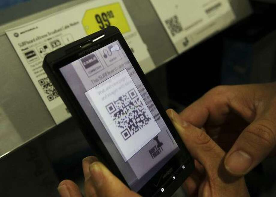 Matt Rinne scans a QR code on a modem price card at Best Buy. Quick Response, or QR, is a matrix bar code readable by dedicated QR bar code readers and camera phones. Photo: Brian Van Der Brug, McClatchy-Tribune News Service