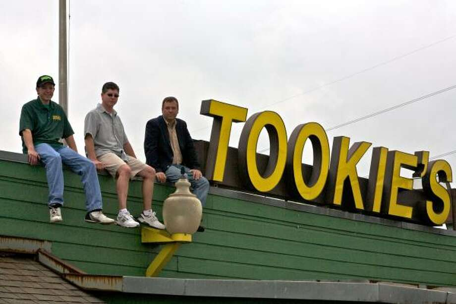 "BURGERMANIA: Tookies, home of the ""Squealer"" hamburger is making a comeback. The restaurant, heavily damaged by Hurricane Ike, is set to reopen in late July and its manager, Jeff Sauerwein, from left, and owners Ali Velasco and Barry Terrell, couldn't be happier about the timing. The eatery first opened July 4, 1975 Photo: Maria-Patricia Cortez, For The Chronicle"