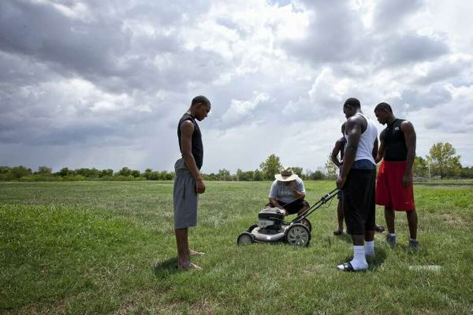 Sterling head coach Eddie Chinea and a few of his players try to start a lawnmower as they work on their practice field. Photo: TODD SPOTH, For The Chronicle