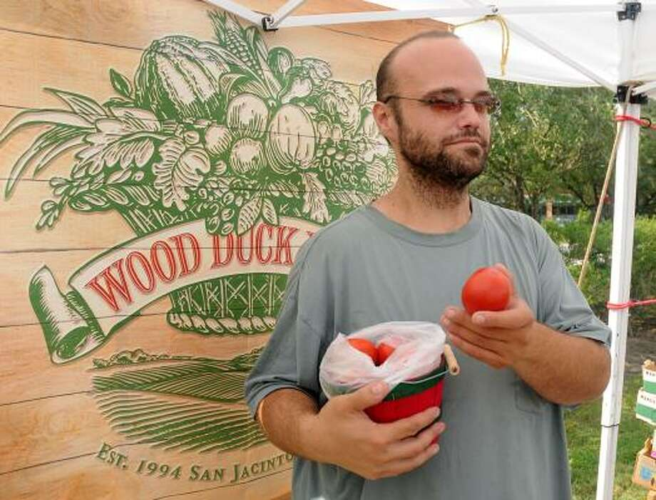 DAVID HOPPER: FOR THE CHRONICLE GARDEN FRESH: Work Duck Farm salesman Jose Estrade shows off the tomatoes for sale at the farm's booth during the Grogan's Mill Village Farmer's Market at Grogan's Mill Village Shopping Center. Photo: David Hopper, For The Chronicle