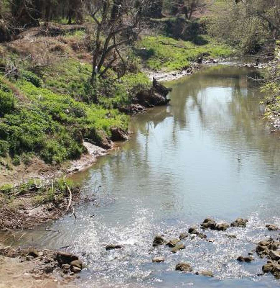 COURTESY OF THE HARRIS COUNTY FLOOD CONTROL DISTRICT AFTER THE CLEANUP: This is a section of Little White Oak Bayou near Woodland Park in Houston's Woodland Heights neighborhood after the Harris County Flood Control District removed underbrush and trees, and pruned trees with low-hanging limbs along the bayou. Approximately 900 cubic yards of debris was removed from the bayou.