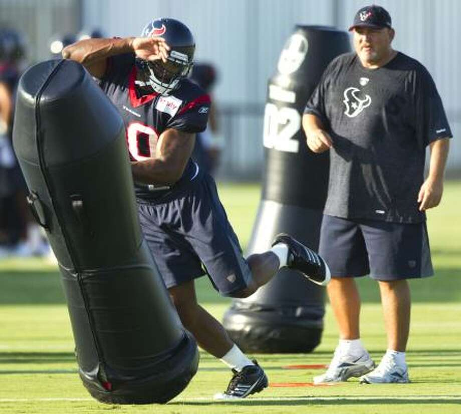 Mario Williams, left, hits a blocking dummy as linebackers coach Reggie Herring looks on during training camp. Photo: Brett Coomer, Chronicle