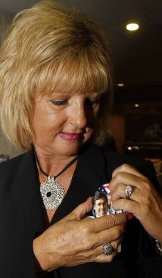 Janice Finn tries on a Rick Perry button at the Republican summer dinner in Birmingham, Ala. Photo: Butch Dill, Associated Press