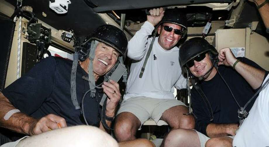 Texans head coach Gary Kubiak, center, takes a ride in an Mine Resistant Ambush Protected vehicle with Jim Mora, left and Jim Mora Jr. Photo: Courtesy Of USO