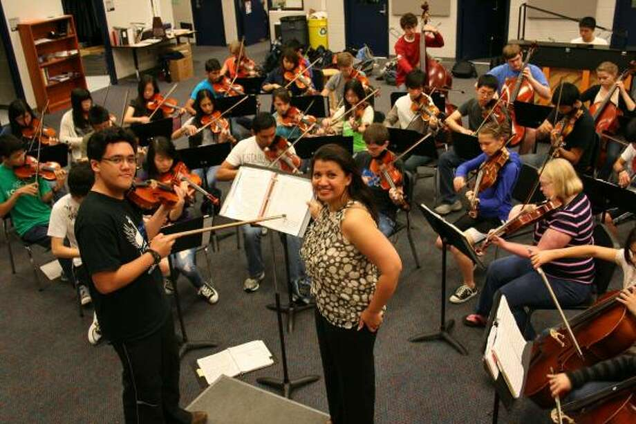 HONORED MUSICIAN: Seven Lakes High School 2010 graduate R.J. Cruz, left, works with Seven Lakes High School orchestra director Desiree Overree and members of the Seven Lakes HS orchestra. Cruz wrote an original piece of music, Guardian Souls of the Alamo, that was recently recognized with an Honorable Mention Certificate in the 2010 Original Score Contest presented by State Farm. Photo: COURTESY, SEVEN LAKES HIGH SCHOOL