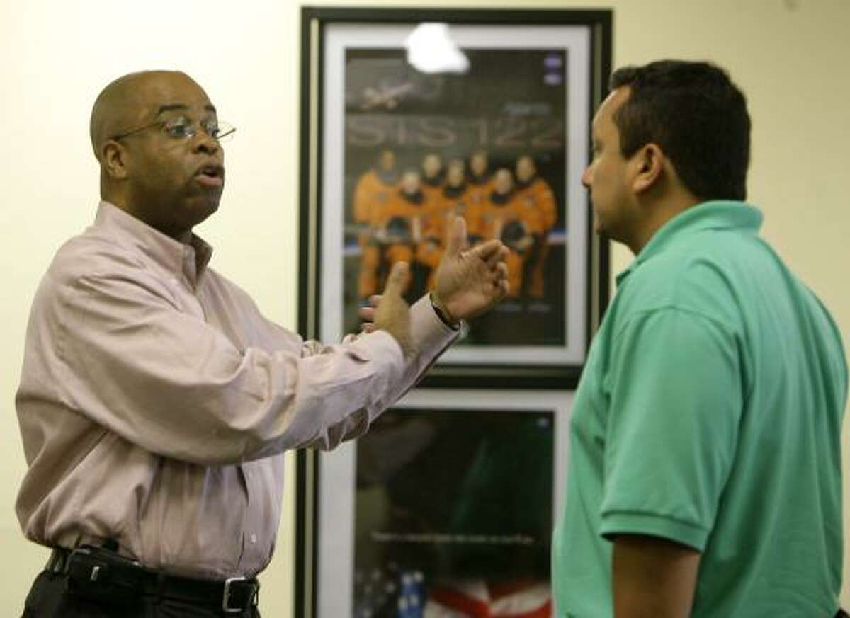 Astronaut memorabilia line the walls of the Aerospace Transition Center, where financial aid specialist Valentino Murphy, left, chats with job seeker David Quinones on Monday,