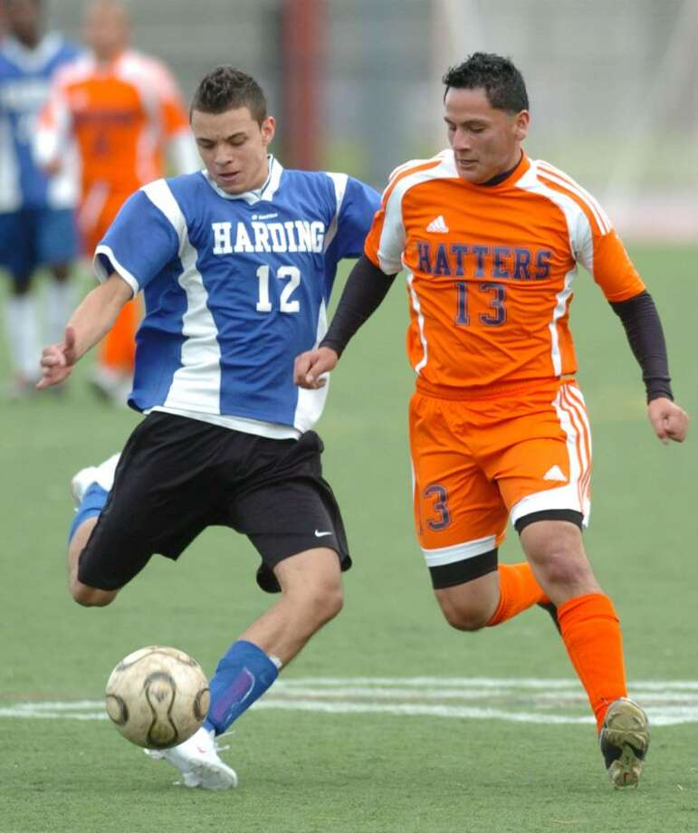 Danbury's 13, Andres Vera and Harding's 12, George Perez, play soccer against Harding at Danbury High Wednesday, Oct. 14, 2009. Photo: Chris Ware / The News-Times