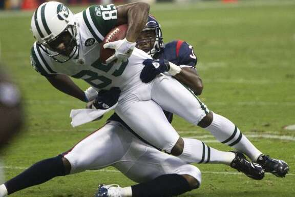 Jets wide receiver Derrick Mason (85) is stopped by Texans safety Danieal Manning during the first half.