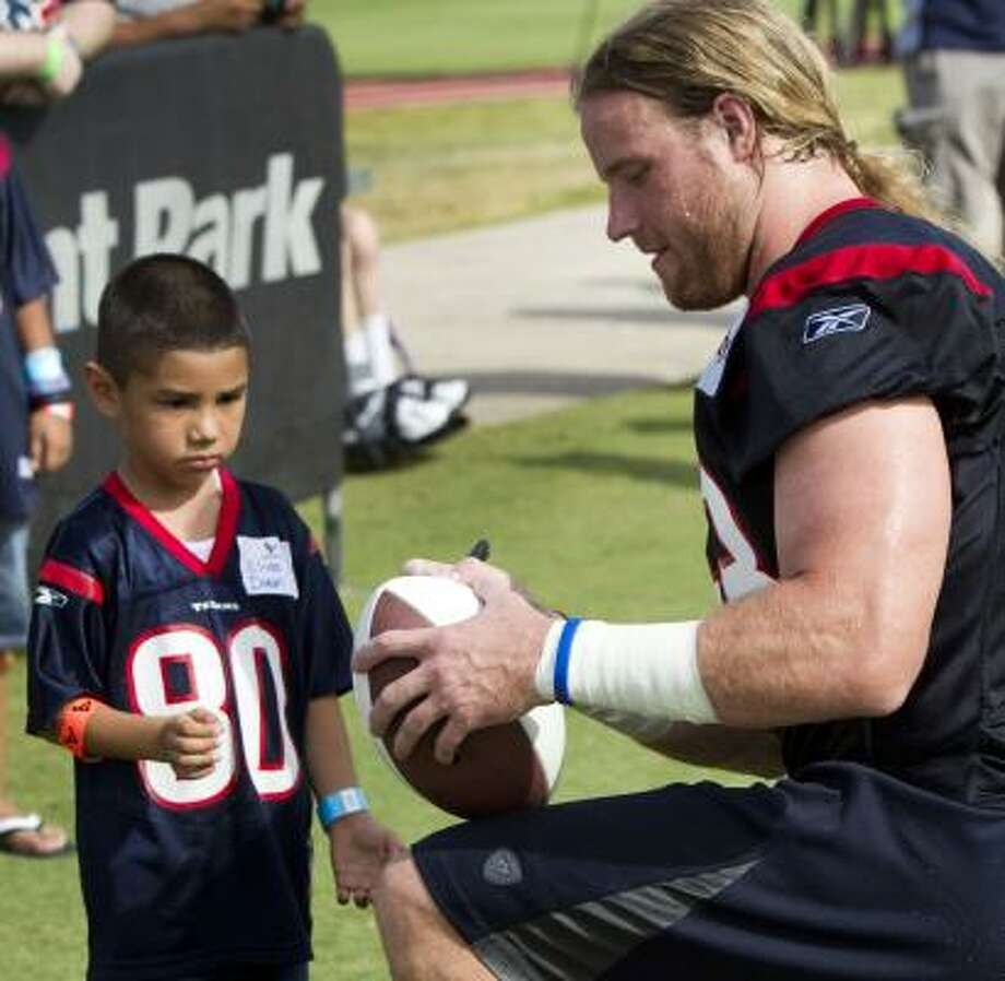 Texans linebacker Brooks Reed signs a ball for young Texans fan Elias Duran. Photo: Brett Coomer, Chronicle