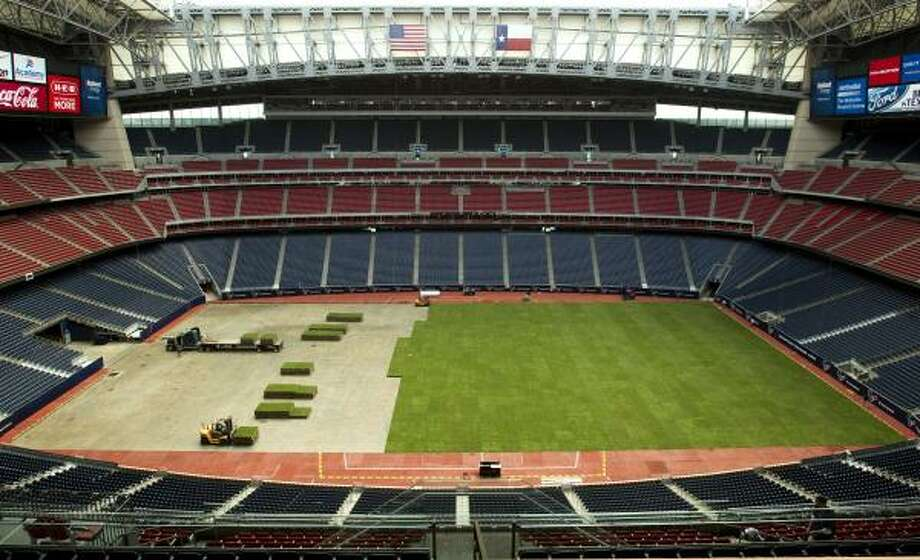 The squares of grass are brought to the floor of Reliant Stadium. The field is being pieced together in preparation for the Texans first preseason game Monday night against the Jets. Photo: Brett Coomer, Chronicle